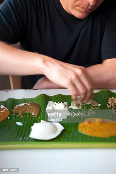 A man eating Idli steamed cakes of rice and black lentils that arrive on a banana leaf and are served with the quartet of chutneyscoconut tomato...