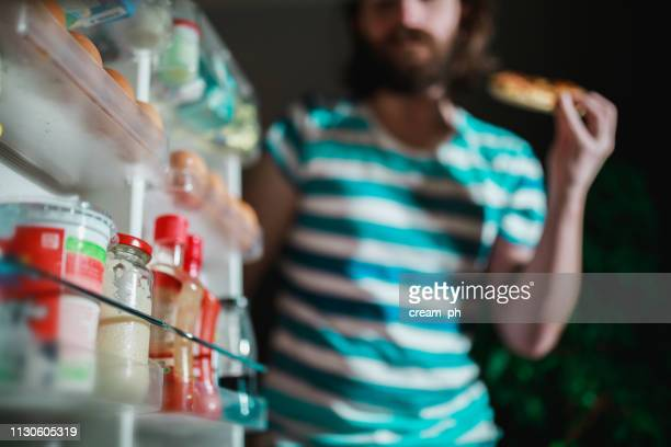 man eating in front of the refrigerator late night - eating disorder stock pictures, royalty-free photos & images