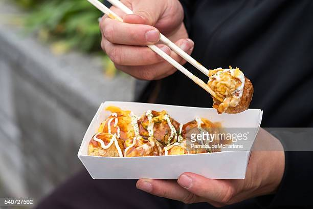 man eating japanese street food with chopsticks, takoyaki octopus balls - street food stock pictures, royalty-free photos & images
