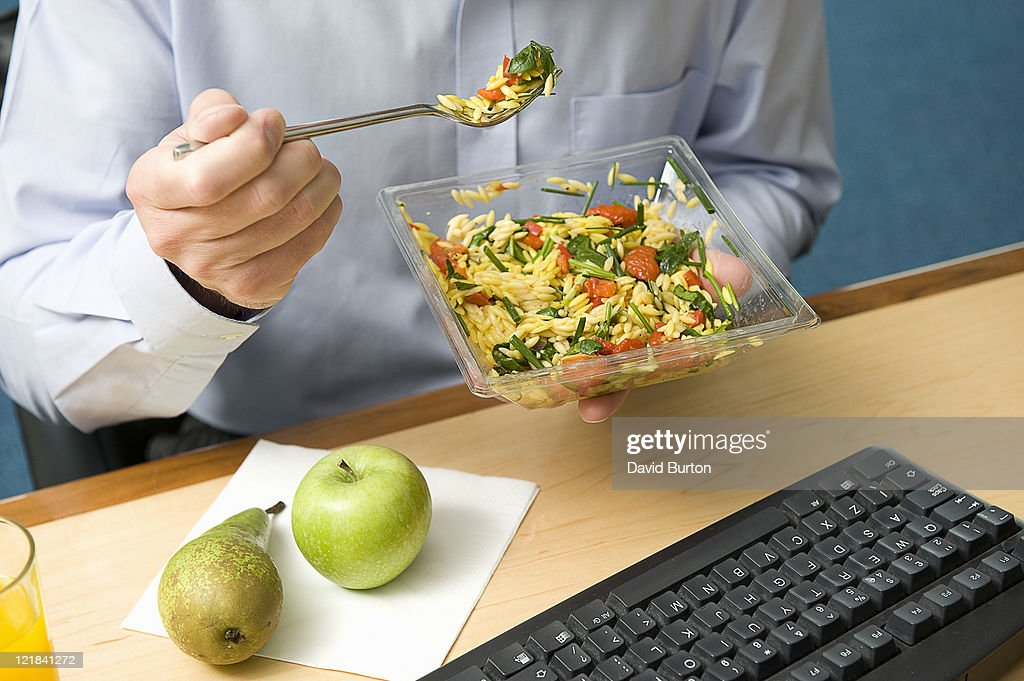 Man eating lunch at work : Stock Photo