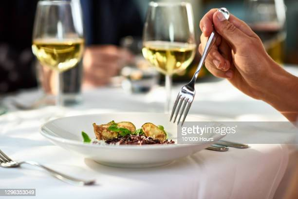 man eating meal at table with fork - gourmet stock pictures, royalty-free photos & images