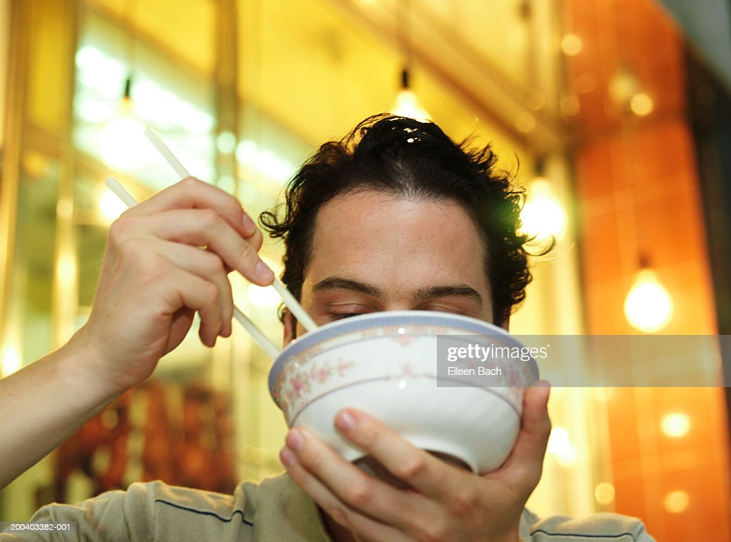 Man eating noodles, bowl obscuring face, low angle view : Stock Photo