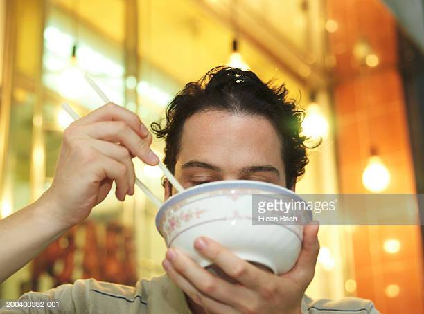 Man eating noodles, bowl obscuring face, low angle view