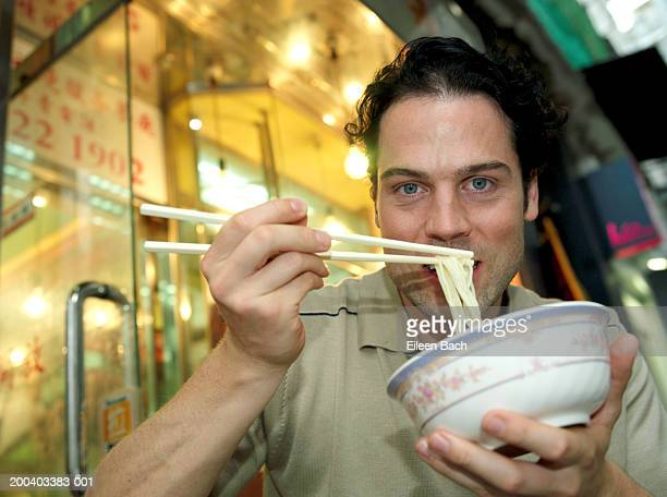Man eating noodles, portrait, low angle view