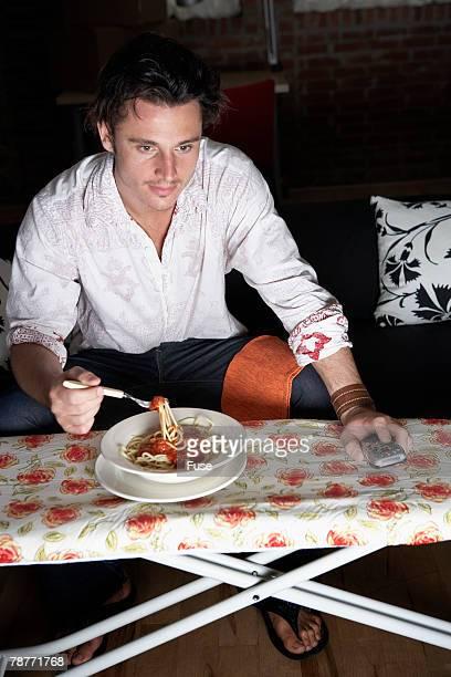 Man Eating on Ironing Board