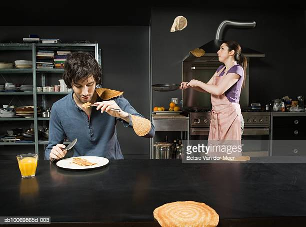 man eating pancake, while woman turning them in pan - pancakes stock pictures, royalty-free photos & images