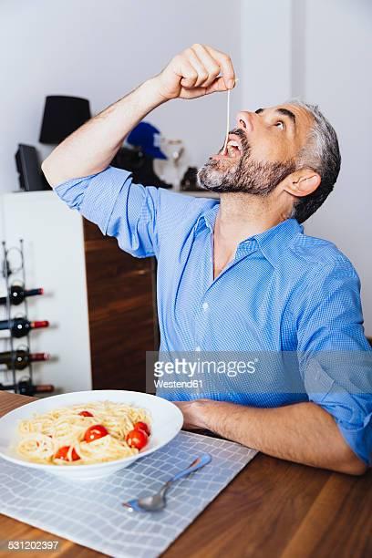 Man eating pasta in his kitchen