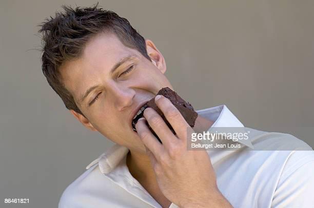 Man eating piece of cake