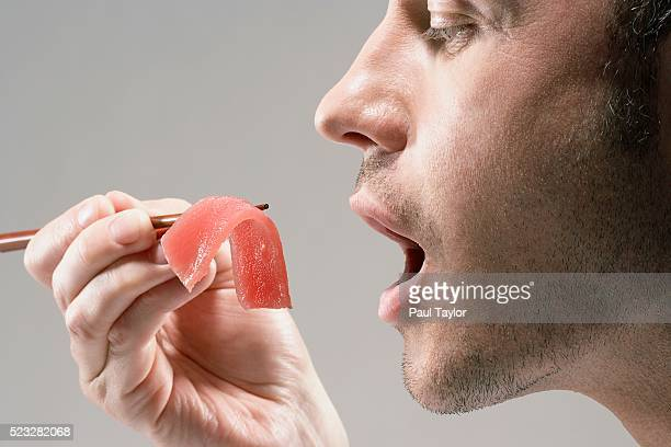 man eating piece of sashimi - mouth open stock pictures, royalty-free photos & images