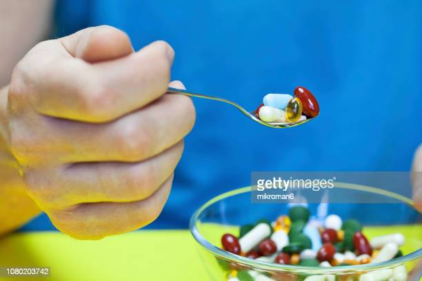 man eating pills, medical concept - sexually transmitted disease stock photos and pictures