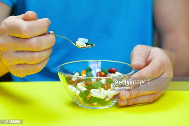 man eating pills, medical concept - pain relief stock pictures, royalty-free photos & images