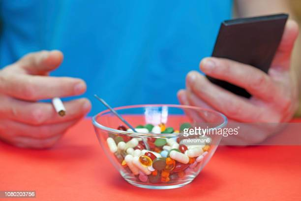 man eating pills, smoking cigarette and using smartphone. medical concept - sexually transmitted disease stock photos and pictures