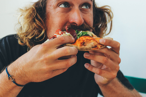 Man eating pizza in a restaurant 936000778