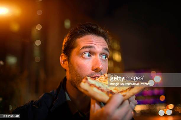 Man eating pizza on city street