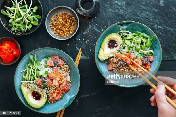 man eating poke bowls with ponzu dressing - bowl stock pictures, royalty-free photos & images