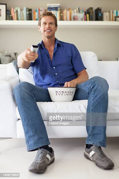 man eating popcorn and watching tv - changing channels stock photos and pictures