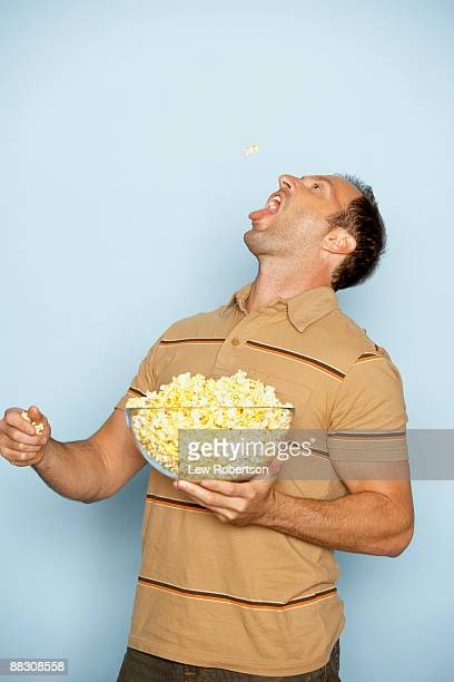 man eating popcorn - mouth open stock pictures, royalty-free photos & images