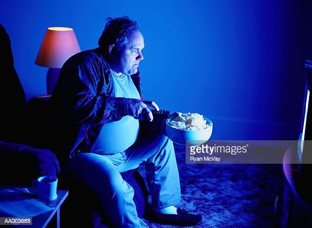 man eating potato chips and watching television - pancia gonfia foto e immagini stock