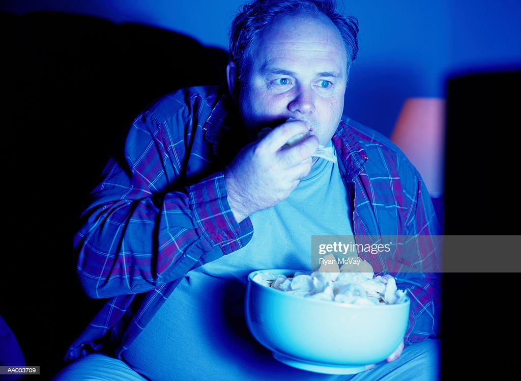 Man Eating Potato Chips and Watching Television : ストックフォト