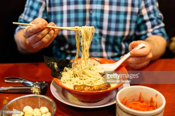 man eating ramen at japanese restaurant - ramen noodles stock pictures, royalty-free photos & images