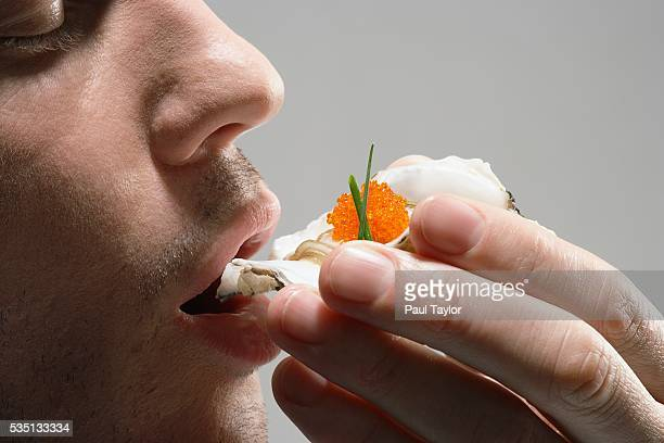 Man eating raw oyster in the shell