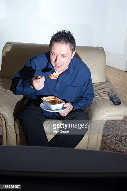 Man eating ready meal alone in front of TV UK