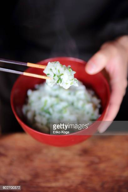 man eating rice porridge with seven herbs of spring called nanakusa gayu - congee stock photos and pictures
