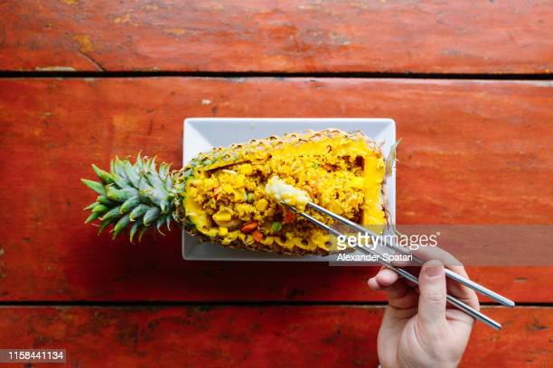 man eating rice with chopsticks from a pineapple, directly above view - exotismo fotografías e imágenes de stock