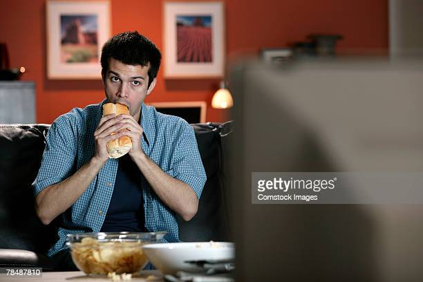 man eating sandwich and watching television - submarine sandwich stock pictures, royalty-free photos & images