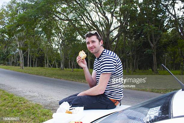 Man eating sandwich on trunk of car