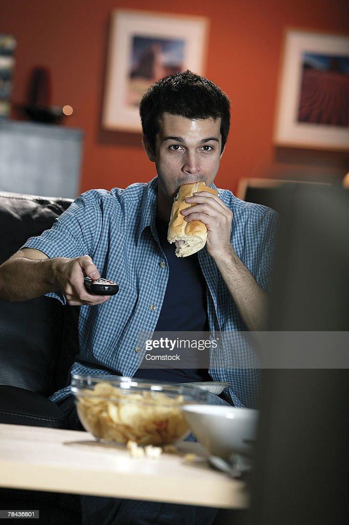 Man eating sandwich while watching TV : Stockfoto