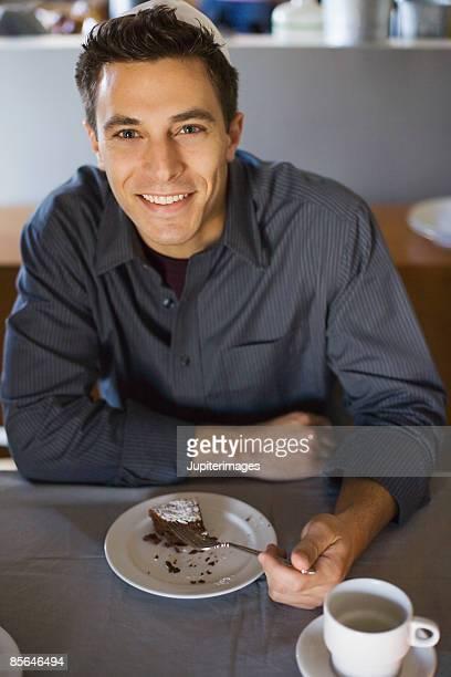 Man eating slice of chocolate cake