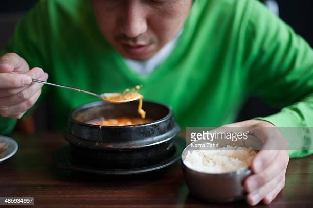 Man eating soondooboo chigae with rice