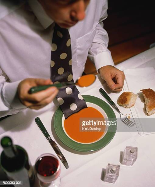 Man eating soup in restaurant, with tie resting in bowl, elevated view