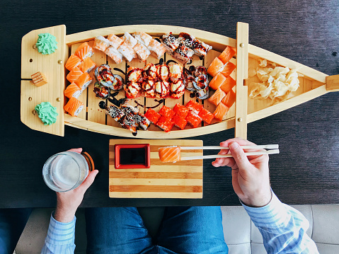 Man eating sushi from a sushi boat in Japanese restaurant, directly above personal perspective view - gettyimageskorea
