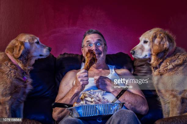 man eating the last turkey dinner drumstick on couch as 2 dogs watch - dog turkey stock pictures, royalty-free photos & images