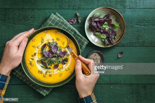 mann essen vegan cremige geröstete kürbissuppe - herbst winter kollektion stock-fotos und bilder