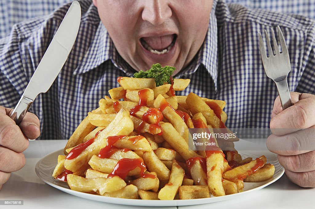 Man eating very large plate of fries : Stock Photo