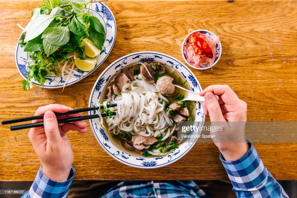 Man eating Vietnamese Pho soup with noodles and beef, personal perspective view : Stock Photo