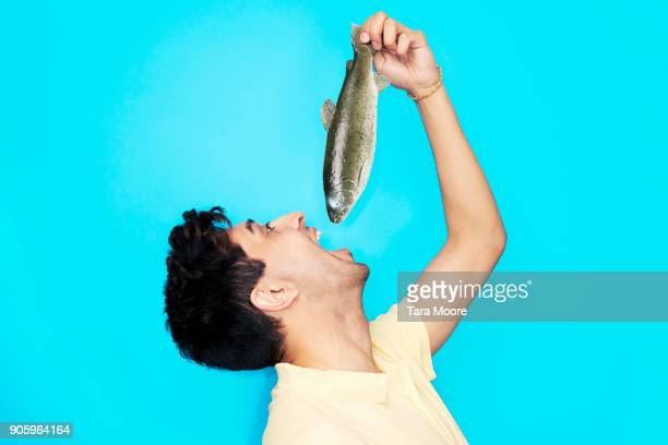 man eating whole fish - incidental people stock pictures, royalty-free photos & images