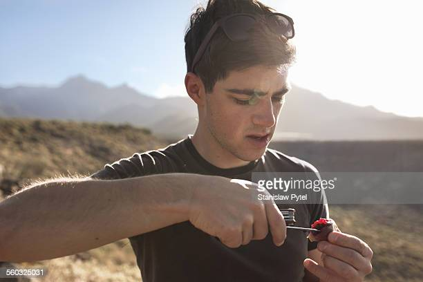 Man eating wild prickly pear using knife