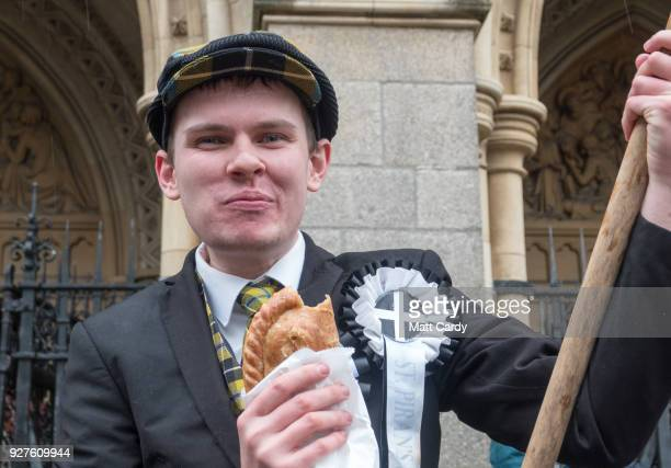 A man eats a Cornish pasty as he attends the St Piran's Day march which celebrates St Piran patron saint of tinners and regarded by many as...