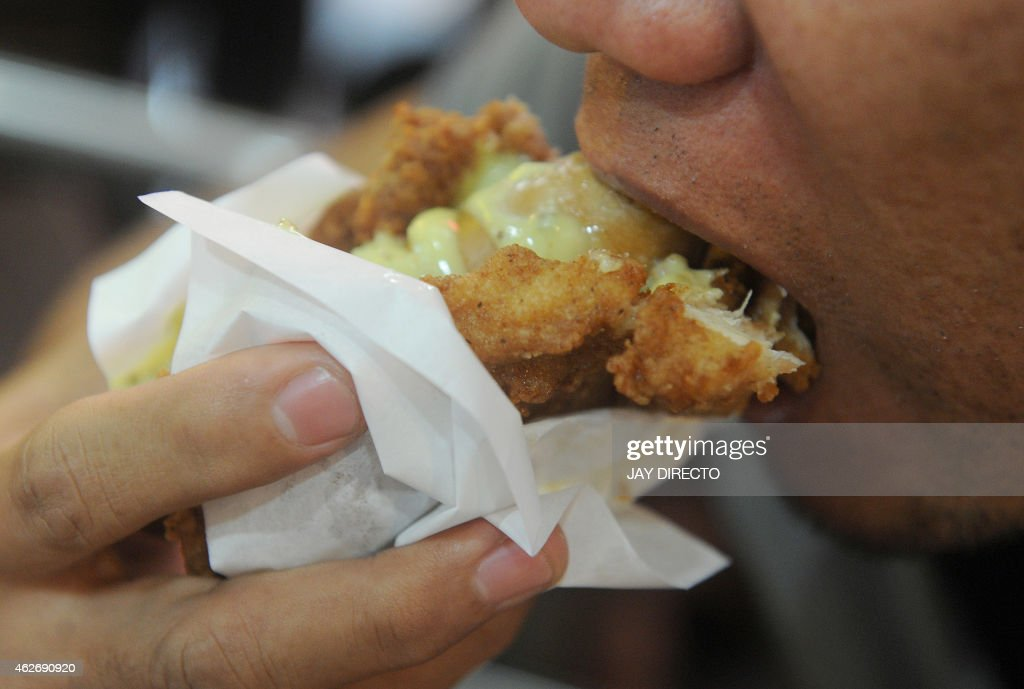 A man eats a 'Double Down Dog,' in Manila on February 3, 2015, a product conceived and introduced by the Philippine franchise of KFC. Fastfood giant KFC in the Philippines has begin selling a hotdog wrapped in fried chicken instead of bread and covered in cheese sauce to the horror of dieticians and amusement of social media users. AFP PHOTO / Jay DIRECTO