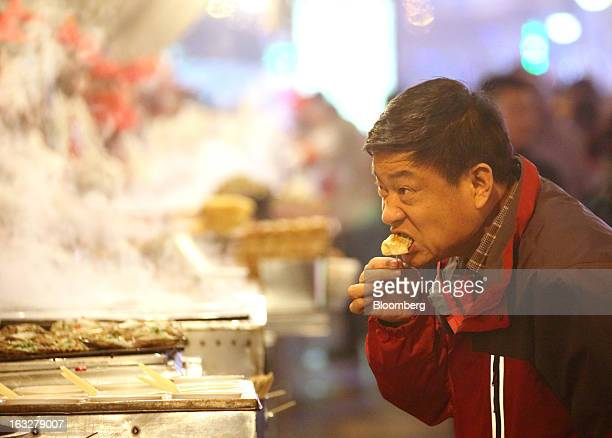 A man eats a dumpling at a stall in a market at night in Beijing China on Wednesday March 6 2013 China maintained its economicgrowth target at 75...