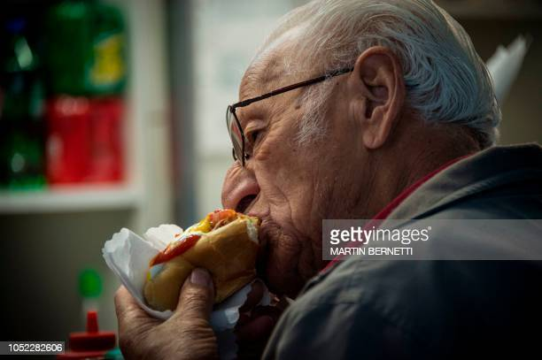A man eats a hot dog at a fast food stand in downtown Santiago on October 16 2018 The nutritional prospect of the Chilean population is critical due...