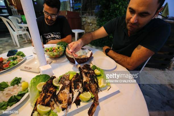 A man eats a lionfish an invasive nonnative carnivorous and venomous fish in Batroun on April 14 2018 After colonising parts of the Atlantic on the...