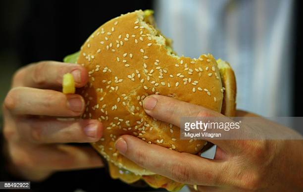 A man eats a Whopper during the opening of the first European Whopper Bar on June 15 2009 in Munich Germany Customers can choose from over 20...