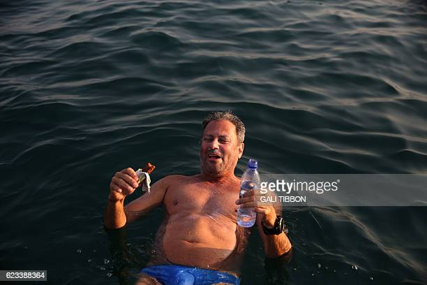 A man eats and drinks while floating during a 17kilometre swim from Jordan to Israel across the Dead Sea organised by the EcoPeace charity aimed at...