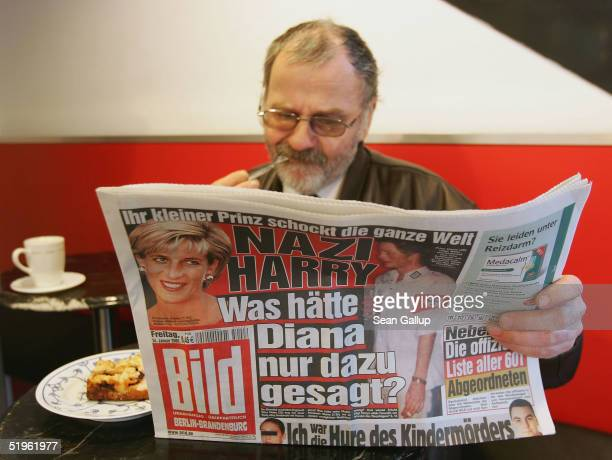 A man eats cake while reading the day's issue of the German tabloid 'Bild' which features the story of British Prince Harry attending a party dressed...