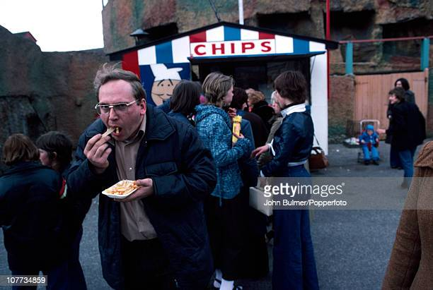 A man eats chips from a carton outside a chip stand in Manchester England in 1976